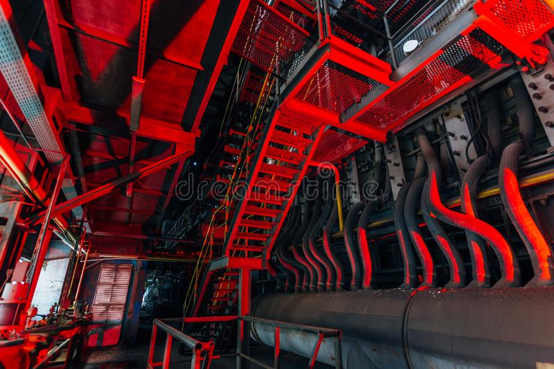 Inside of old abandoned factory. Rusty ruined industrial pipeline connection. Abstract red illuminated industrial background.  stock photo