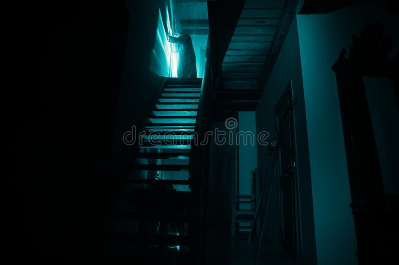 Inside of old creepy abandoned mansion. Silhouette of horror ghost standing on castle stairs to the basement. Spooky dungeon stone stock photos