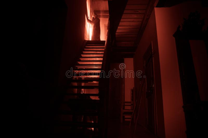 Inside of old creepy abandoned mansion. Silhouette of horror ghost standing on castle stairs to the basement. Spooky dungeon stone stock images