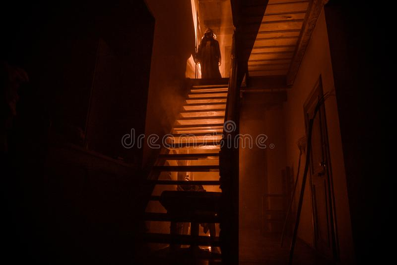 Inside of old creepy abandoned mansion. Staircase and colonnade. Silhouette of horror ghost standing on castle stairs to the royalty free stock photo