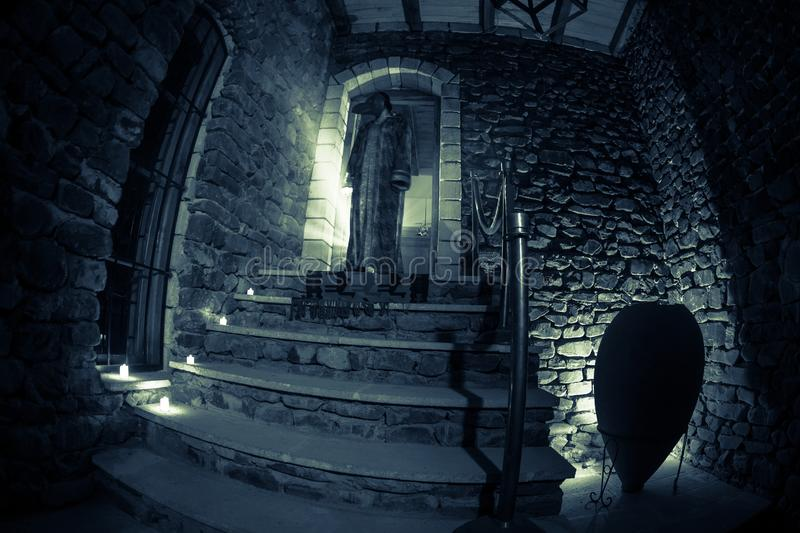 Inside of old creepy abandoned mansion. Staircase and colonnade. Silhouette of horror ghost standing on castle stairs to the basem. Inside of old creepy stock photo