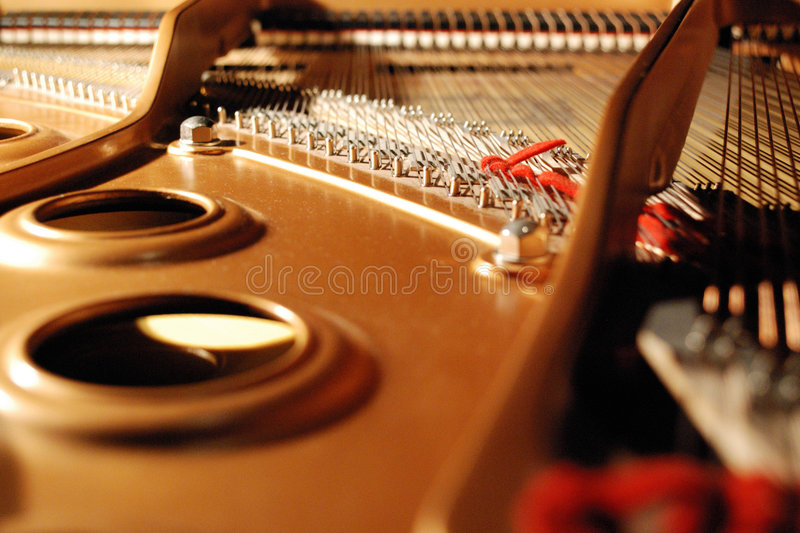 Inside a grand piano. With strings and metal - Red ribbon to absorb unwanted vibrations royalty free stock photos