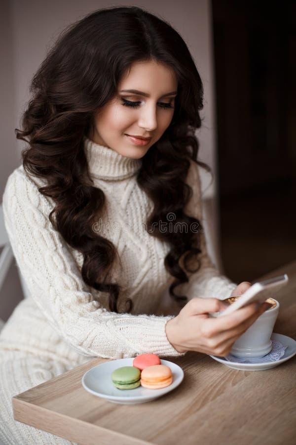 Inside portret uśmiechnięta kobieta z długie włosy pisze wiadomości Na kawie, cukierkach i macaroons stołowych, zdjęcie royalty free