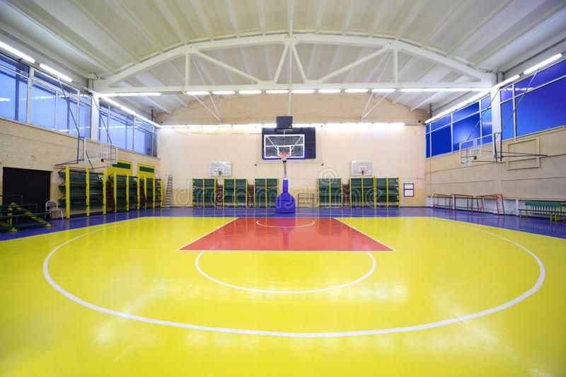 Inside school gym hall with red-yellow floor. Inside lighted school gym hall with red-yellow floor and basket royalty free stock image