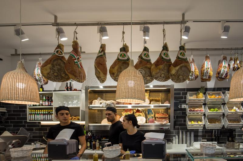 Inside small Italian food and mini market with staff at work in Ferrara. Italy stock photo
