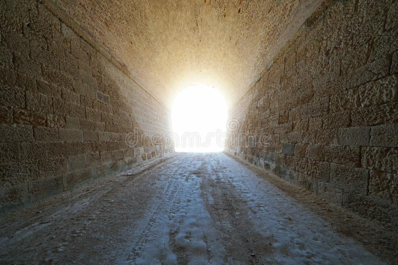Inside a tunnel with bright light at the end royalty free stock image