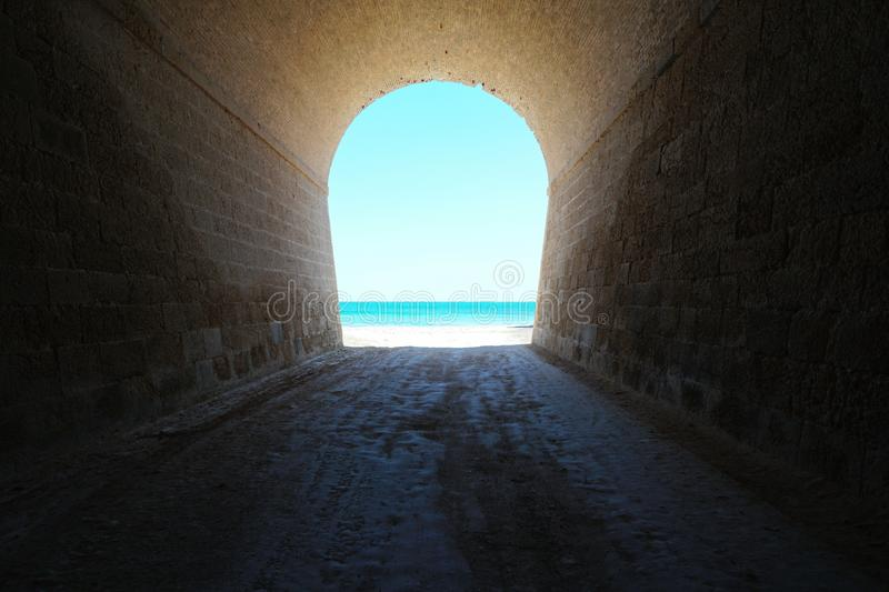 Inside a tunnel leads to sea shore natural scene royalty free stock images