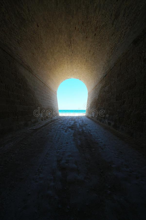 Inside tunnel that leads to seashore natural scene stock photo