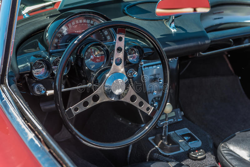 Inside view of a Classic American Sports Car. With black interior and red exterior. Closeup of the steering wheel and dash royalty free stock image