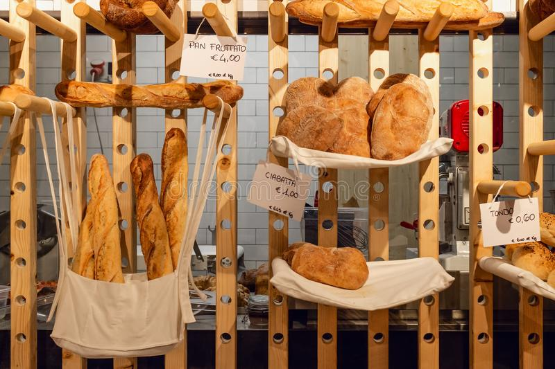 Inside view of an italian bakery shop with the kitchen in background and different bread types. Pan fruttato fruity bread, ciabatta ciabatta bread and tondo royalty free stock images