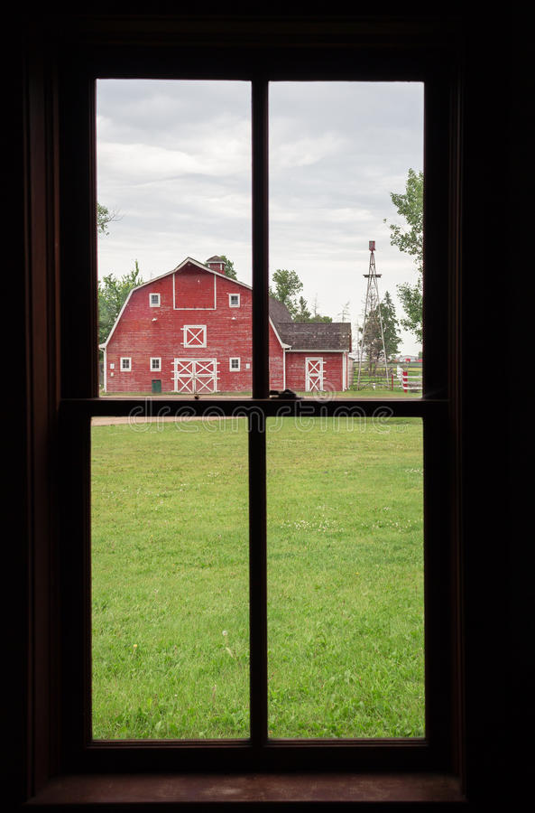 Inside view looking out at an old red barn in summertime. stock images