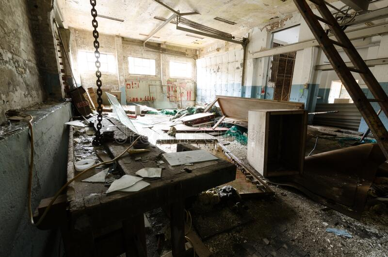 Inside view of an abandoned machine shop with debris and damaged equipment in Ivittuut Greenland. Inside view of an old abandoned machine shop with debris and royalty free stock photo
