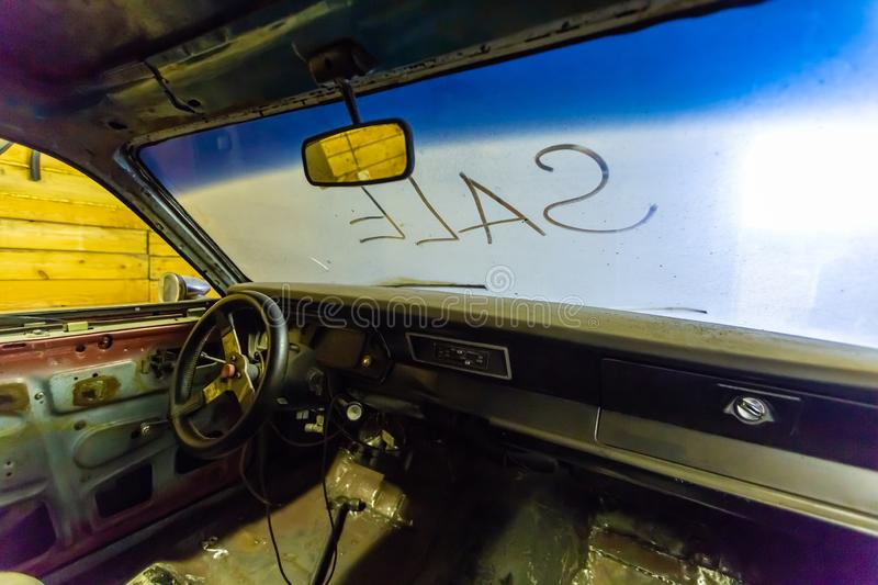 Inside view of old broken car interior with dusty vehicle dashboard, back mirror, driving steering wheel and dirty wind. Screen with title SALE written outside stock images