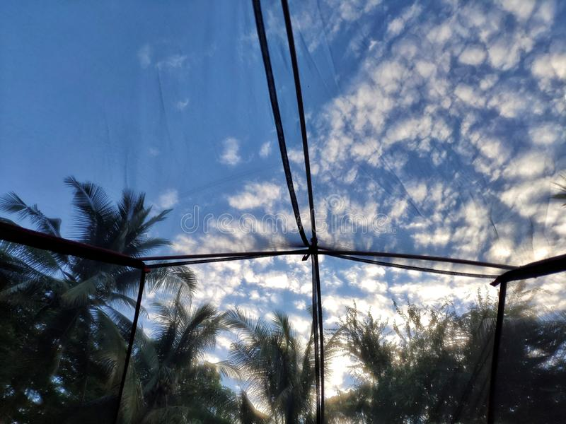 Inside view from a tent of beautiful blue sky with clouds. Inside view from the tent of beautiful blue sky with clouds royalty free stock images