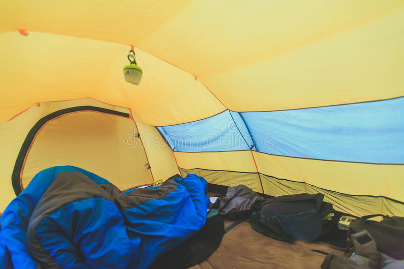 An inside view of tent, process of camping in fall or spring forest field, setting a tent covered stock photography