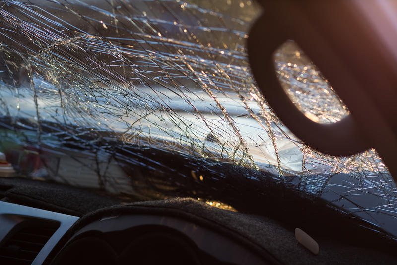 Inside windshield cracks. Close-up details of the inside of the windshield is cracked due to an accident with another vehicle, severely stock photography