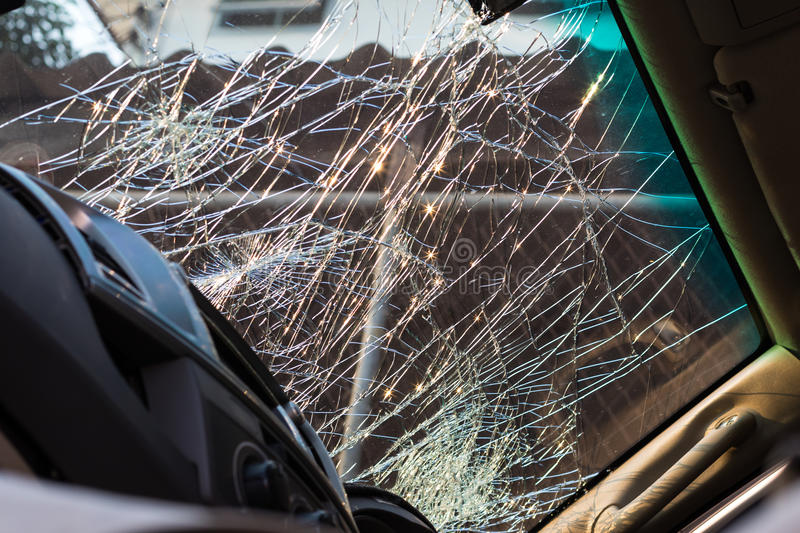 Inside windshield cracks. Close-up details of the inside of the windshield is cracked due to an accident with another vehicle, severely royalty free stock images