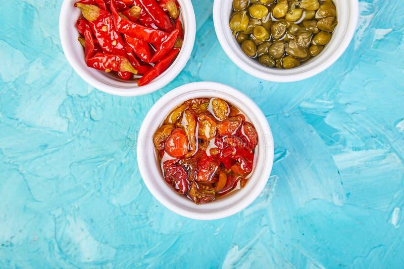 Insieme conservato italiano - capperi e pepe marinati, pomodori seccati al sole fotografia stock