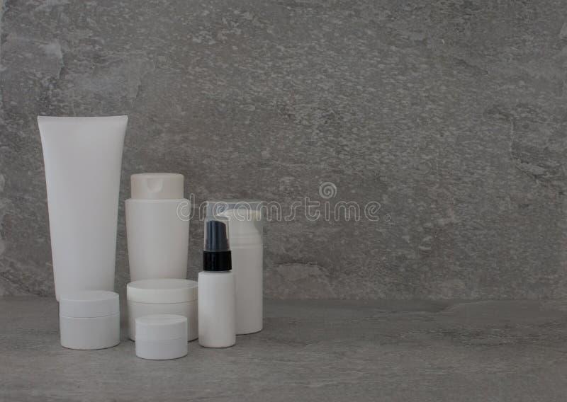 Insieme d'imballaggio cosmetico su fondo grigio gruppo di olio del siero della crema dello skincare prodotto cosmetico della staz immagini stock libere da diritti