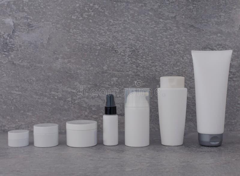 Insieme d'imballaggio cosmetico su fondo grigio gruppo di olio del siero della crema dello skincare prodotto cosmetico della staz immagini stock