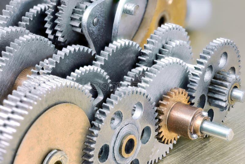 Insieme degli ingranaggi meccanici d'acciaio su fondo d'ottone industriale immagine stock