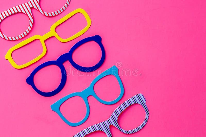 Insieme degli occhiali variopinti della cabina della foto su fondo rosa con la c fotografie stock libere da diritti