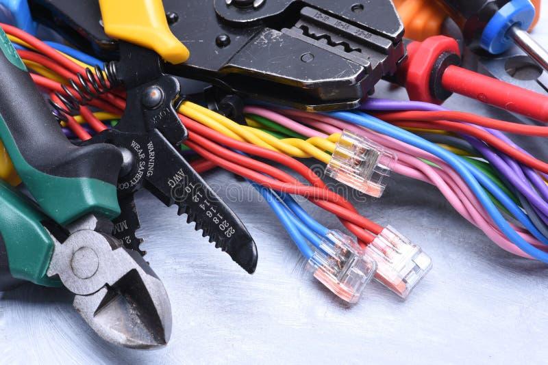 Insieme degli strumenti per l'elettricista ed i cavi elettrici fotografia stock libera da diritti