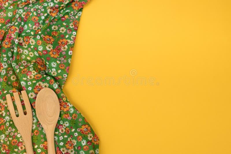 Insieme degli utensili di legno della cucina Tovagliolo floreale del panno del modello sulla e fotografia stock libera da diritti