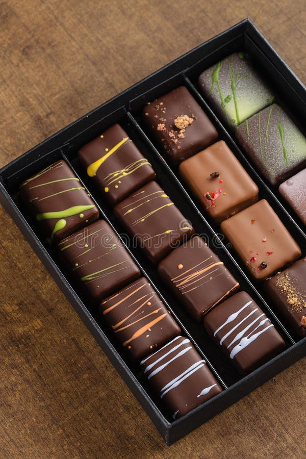 Insieme dei bonbon fatti a mano di lusso in un contenitore di regalo su backgroun di legno fotografia stock