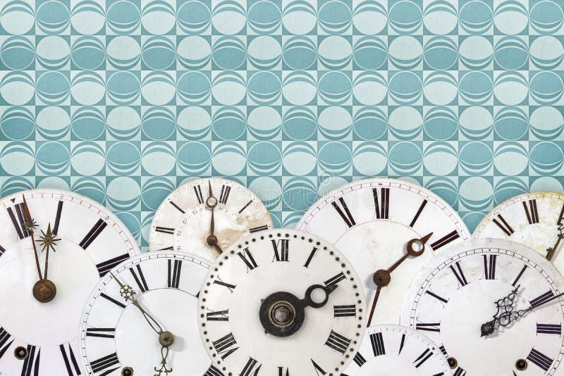 Insieme dei fronti di orologio d'annata contro un retro fondo della carta da parati fotografie stock