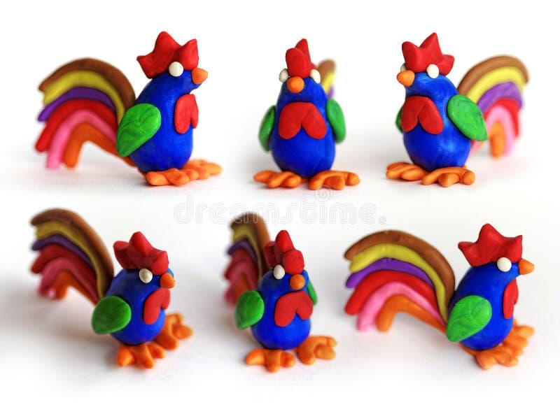 Insieme dei galli del plasticine nelle viste differenti Galli dell'argilla da modellare isolati su fondo bianco Simbolo cinese de fotografia stock libera da diritti