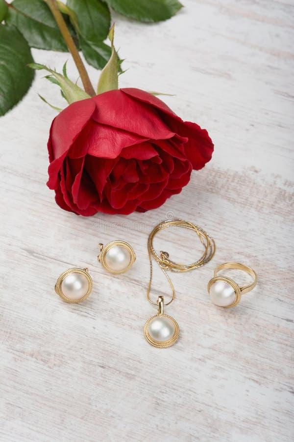Insieme dei gioielli dell'anello dorato, degli orecchini, della collana con le perle e della rosa rossa su fondo di legno bianco immagini stock