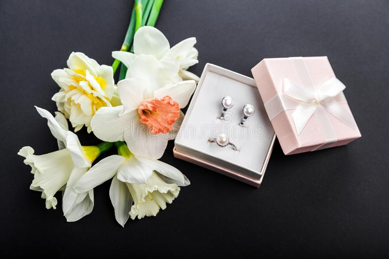 Insieme dei gioielli della perla in contenitore di regalo con i fiori Orecchini ed anello d'argento con le perle come presente pe fotografie stock libere da diritti