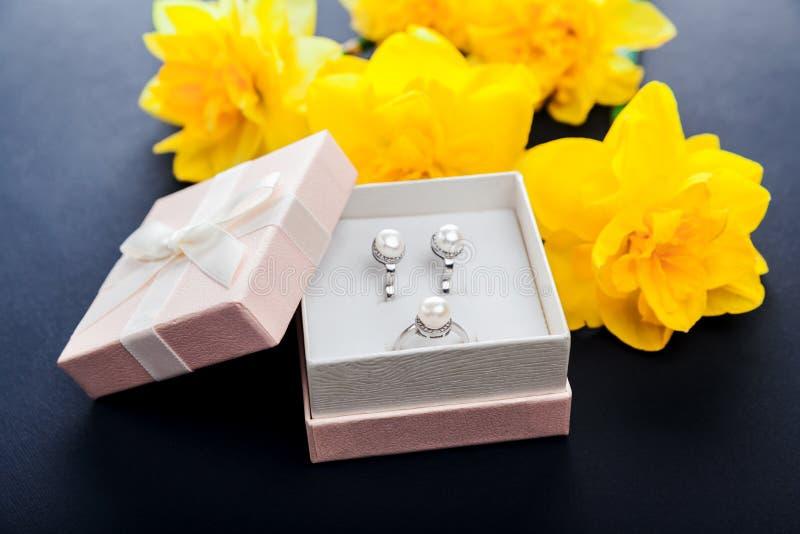 Insieme dei gioielli della perla in contenitore di regalo con i fiori Orecchini ed anello d'argento con le perle come presente pe immagine stock