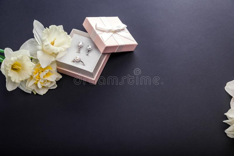 Insieme dei gioielli della perla in contenitore di regalo con i fiori Orecchini ed anello d'argento con le perle come presente pe immagini stock