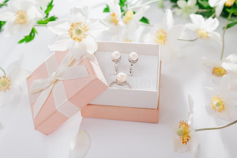 Insieme dei gioielli della perla in contenitore di regalo con i fiori Orecchini ed anello d'argento con le perle come presente pe fotografie stock