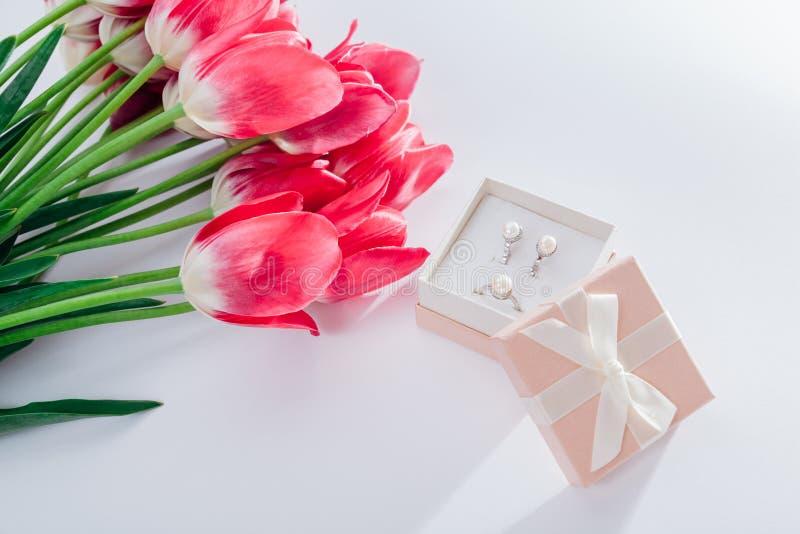 Insieme dei gioielli della perla in contenitore di regalo con i fiori Orecchini ed anello d'argento con le perle come presente pe immagini stock libere da diritti