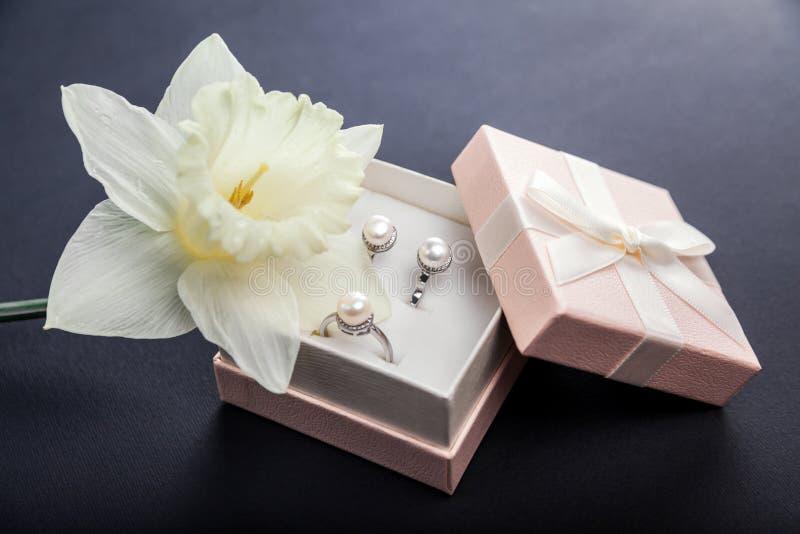 Insieme dei gioielli della perla in contenitore di regalo con il fiore Orecchini ed anello d'argento con le perle come presente p immagine stock libera da diritti