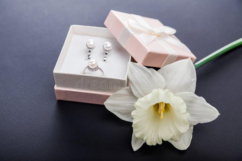 Insieme dei gioielli della perla in contenitore di regalo con il fiore Orecchini ed anello d'argento con le perle come presente p fotografia stock libera da diritti