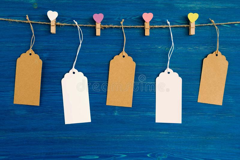 Insieme dei prezzi da pagare o di etichette della carta in bianco e perni di legno decorati sui cuori colorati che appendono su u fotografie stock libere da diritti