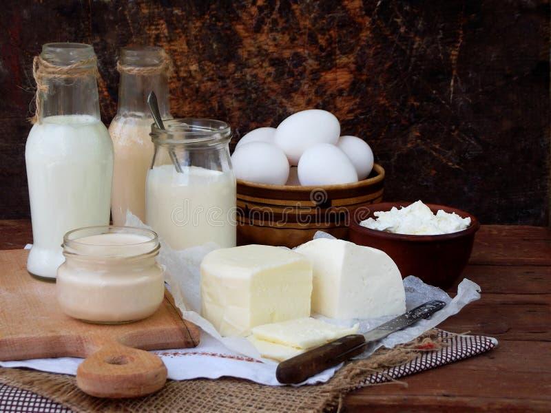 Insieme dei prodotti lattier-caseario freschi su fondo di legno: munga la feta di ryazhenka della mozzarella dell'uovo del yogurt immagine stock libera da diritti
