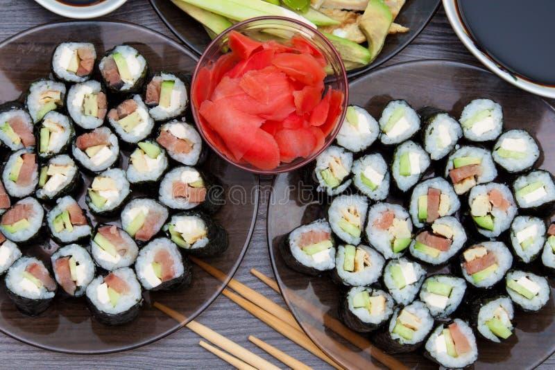 Insieme dei rotoli di sushi servito sul piatto di pietra nero su fondo scuro Disposizione piana, vista superiore Menu giapponese  immagini stock libere da diritti