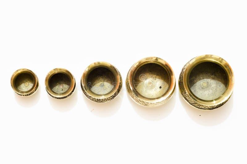 Insieme dei vasi antichi del metallo dell'isolato differente di dimensione su fondo bianco fotografia stock