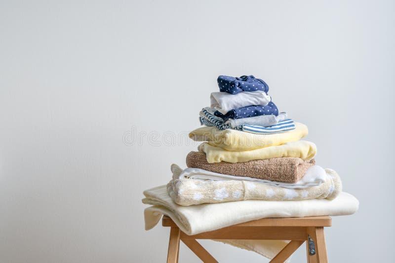 Insieme dei vestiti per un mucchio molle e accogliente del letto di bambino della biancheria intima del tessuto del fondo fotografia stock