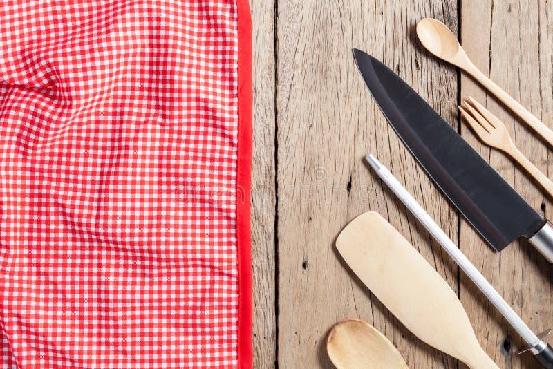 Insieme del cucchiaio di legno, della forchetta, del coltello e del tovagliolo rosso su vecchio tabl di legno immagini stock libere da diritti