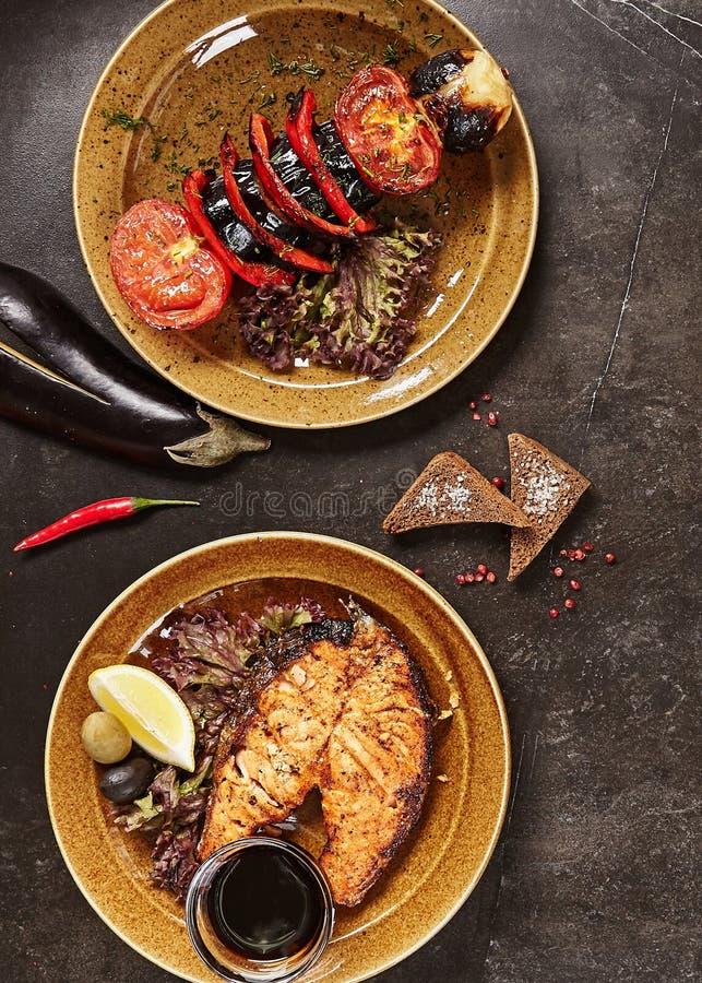 Insieme del pesce arrostito affumicato del BBQ e del punto di vista superiore delle verdure fotografie stock