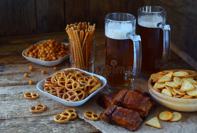 Insieme del tifoso con le tazze di birra e degli spuntini salati su fondo di legno I cracker, ciambellina salata, hanno salato le fotografie stock