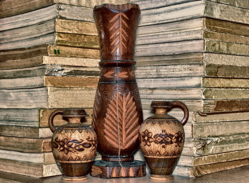 Insieme del vaso e delle tazze di legno su uno scaffale con i libri fotografia stock libera da diritti