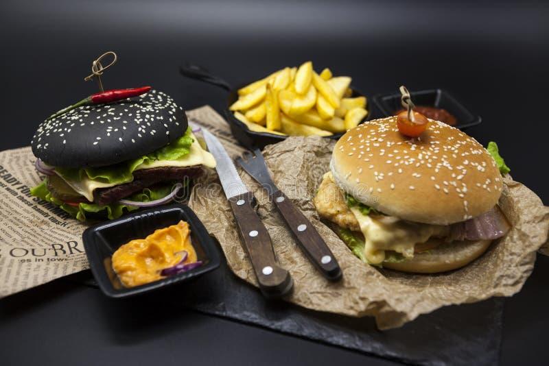 Insieme dell'hamburger nero e dell'hamburger americano classico Fette nere del rotolo dell'hamburger di manzo di marmo succoso, f fotografie stock libere da diritti