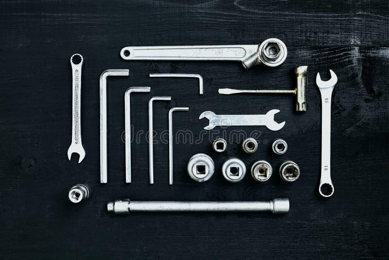 Insieme della chiave degli strumenti della chiave e del cacciavite dell'incavo delle pinze su fondo di legno nero immagini stock libere da diritti